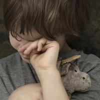 Un enfant s'essuie les yeux en serrant un animal en peluche contre lui.