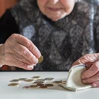 Un dame âgée compte ses sous, posés sur une table devant elle.