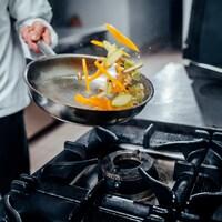 Un cuisiner fait sauter des légumes dans une poêle.