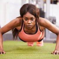 Une femme fait des pompes dans une salle d'entraînement physique.