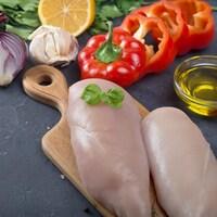 Des poitrines de poulet crues avec des légumes et des assaisonnements sur un comptoir.