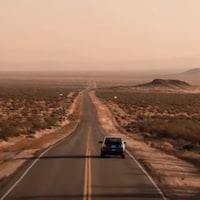 Un voiture roule sur une autoroute dans le désert américain.