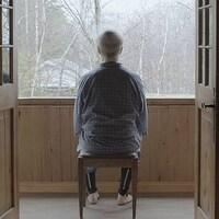 Vue de dos d'un vieil homme qui regarde dehors par une large fenêtre.