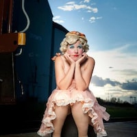 Photographie de la clown Mooky Cornish habillée d'une robe rose pale style années 20. Elle a les paupières bleues et les lèvres rouges. Elle a l'air pensive.