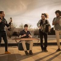 Quatre musiciens côte à côte jouant de leurs instruments.