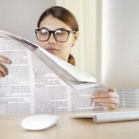 Une femme lit un journal.