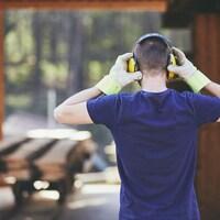 Un travailleur de la construction se protège les oreilles.