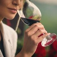 Une femme d'apprête à goûter à un vin rouge.