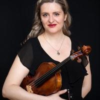 Une femme vêtue de noire tien son violon