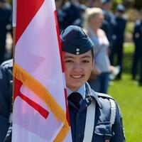 Une jeune fille en uniforme de cadète derrière un drapeau.