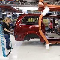 Le châssis d'une voiture en construction avec trois personnes qui installent des pièces dans l'usine Fiat-Chrysler de Windsor.