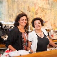 Les deux femmes sourient derrière un comptoir de restaurant.