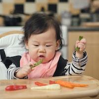 Un bébé mange des aliments solides sur sa chaise haute.
