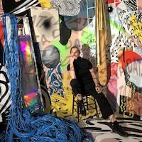 Cyndie Belhumeur pose devant une installation de collages colorés et de fils réseaux.