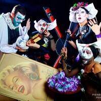 Cinq «bonnes soeurs» avec des maquillages blancs, des cornettes et des costumes osés posent autour d'une photo géante de Marilyn Monroe, avec des accessoires divers et des visages très expressifs.