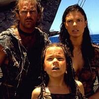 Un couple avec une jeune fille sur un catamaran.