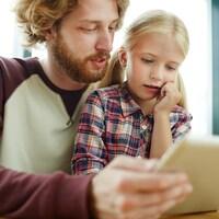 Un père tient une tablette électronique et la montre à sa fille.