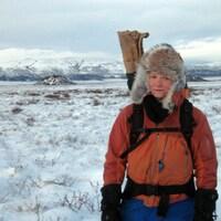 Pascale Roy-Léveillée est debout devant un paysage arctique avec son équipement de recherche dans son sac à dos