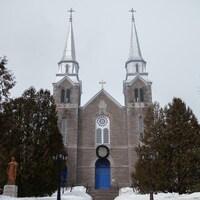 Une église en pierre grise à deux clochers.