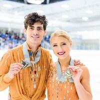 Deux patineurs artistiques posent avec une médaille d'or au cou