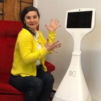 La femme pose à côté d'un robot doté d'un grand écran.