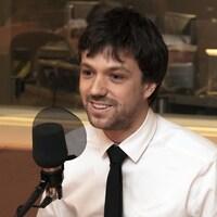 Un jeune homme avec une chemise blanche et une cravate noire parle devant un micro noir dans un studio de radio.
