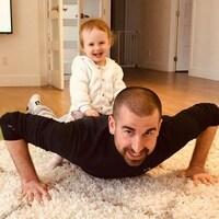 Benoît Huot fait des répulsions (push-ups) avec sa fillette sur le dos.