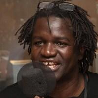 Boucar Diouf parle dans un micro de radio.