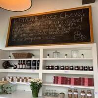Photo d'un grand tableau posé sur des étagères sur lequel il est inscrit : « Bienvenue Chez Cheval. Chez Cheval est un café distinct qui permet à des êtres éblouissants (avec un trouble du spectre de l'autisme) de mettre en lumière la nécessité de leur intégration sociale. »