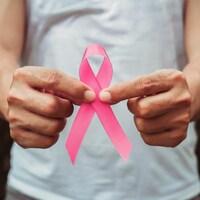 Un homme tient un ruban rose entre ses doigts devant lui.