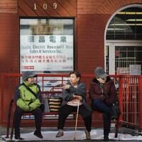 Trois femmes d'origine asiatique discutent, assises sur un banc du quartier chinois de Calgary.