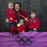 Christine Girard pose sur la plus haute marche d'un podium olympique avec ses trois petits garçons avec une médaille d'or et une médaille de bronze autour du cou.
