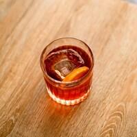 Un cocktail servi dans un verre avec de la glace et une rondelle d'orange.