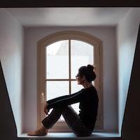 Une femme est assise sur le rebord de sa fenêtre et regarde dehors.