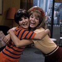 Les deux femmes s'enlacent en souriant à la caméra.