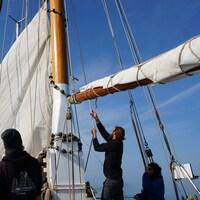Des jeunes se trouvent sur un voilier qui navigue sur le fleuve Saint-Laurent.