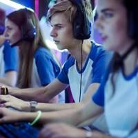 Une équipe de deux filles et de deux garçons jouent sur des ordinateurs.