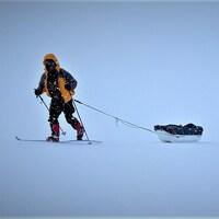 Trois hommes marchent à ski dans la neige en tirant des traîneaux.