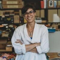 Une jeune femme souriante pose dans son studio d'artiste.