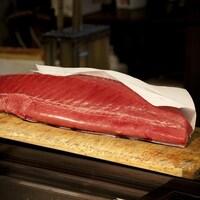Un énorme filet de thon cru posé sur un comptoir en bois.