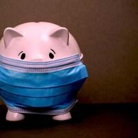 Une tirelire cochon qui porte un masque respiratoire.