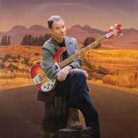 Portrait de François Pérusse assis avec une guitare au milieu d'une route devant un paysage désertique et montagneux.