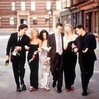 Six amis marchent ensemble, collés les uns sur les autres, dans un décor urbain.