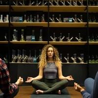 Une jeune femme dans la position du lotus sur un tapis de yoga devant des produits de cannabis.
