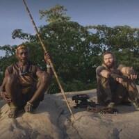 Guillaume Dulude est assis sur un rocher en compagnie de deux autres hommes issus d'une tribu nomade d'Afrique.