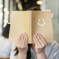 Une femme couvre son visage avec un livre ouvert devant elle sur la couverture duquel un bonhomme sourire est imprimé.