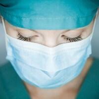 Gros plan sur le visage d'une femme qui porte un masque et une tenue de soignant.