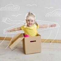 Photo d'une petite fille dans un carton sur laquelle lui est dessiné un costume d'aviatrice.
