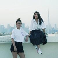 Photo de deux jeunes femmes qui posent devant le paysage d'une ville qui se dessine derrière elles.