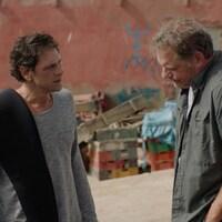 Les deux hommes se parlent dans une cour.